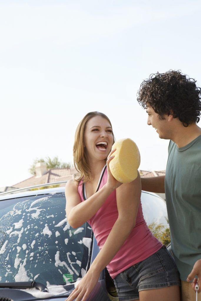 Young couple washing car outdoors