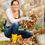 Smiling woman putting leaves in bucket fall garden yardwork